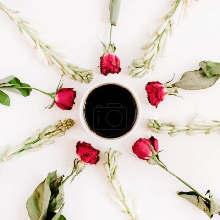 Red roses and white flowers frame with coffee mug