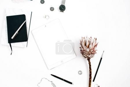 Photo pour Espace de travail blogueur ou pigiste avec tablette écran vierge, fleur de protéa, carnet, montres et accessoires féminins sur fond blanc. Couché plat, vue sur le dessus minimaliste décoré bureau à domicile . - image libre de droit