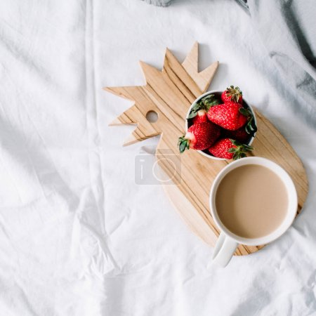 Breakfast in bed with coffee mug and strawberry