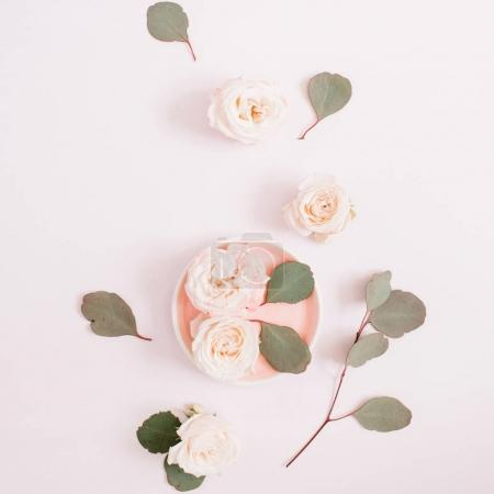 Photo for Beige roses and eucalyptus branches on pale pastel pink background. Flat lay, top view. Floral texture background. - Royalty Free Image