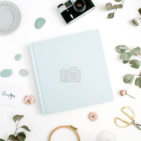 Photo for Blue family or wedding photo album  with blank space for text, eucalyptus leaf, retro camera and dry rose buds on white background. Flat lay, top view. - Royalty Free Image