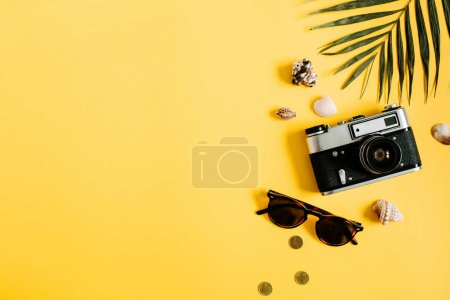 Photo for Flat lay traveler accessories on yellow background with palm leaf, camera and sunglasses. Top view travel or vacation concept. Summer background. - Royalty Free Image
