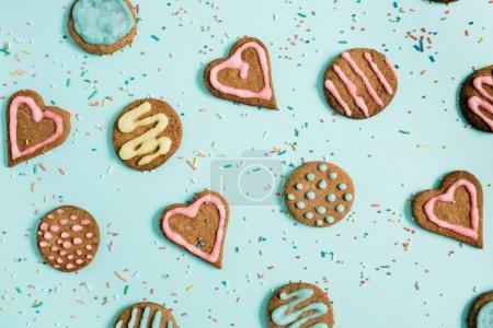 Photo pour Biscuits colorés faits à la main et confettis sur fond bleu. Couché plat, vue du dessus . - image libre de droit