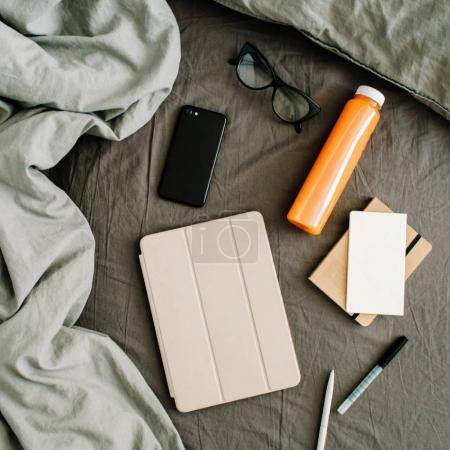 Tablet, diary, mobile, fresh juice, glasses in bed with grey sheet
