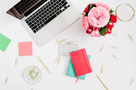 Photo for Flat lay home office desk. Female workspace with laptop, pink and red roses bouquet, golden accessories, red and mint diary on white background. Top view feminine background. - Royalty Free Image