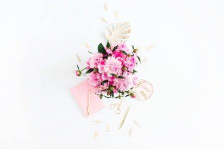 Photo pour Bureau plat laïcs Bureau à domicile. Espace de travail féminin avec bouquet de pivoines roses, accessoires dorés, journal rose sur fond blanc. Vue de dessus fond féminin. - image libre de droit