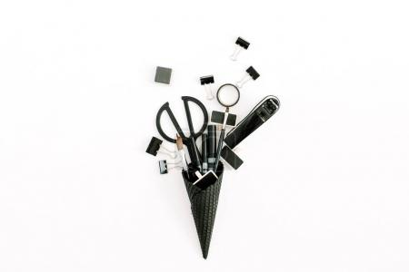 Black ice cream waffle cone with office stationery tools