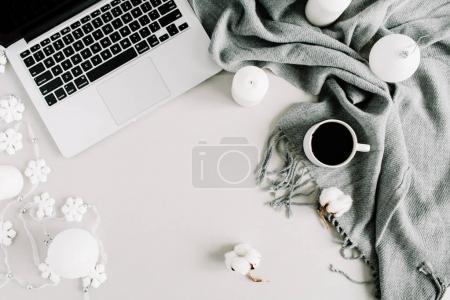 Home office desk with laptop, plaid, candles, cotton balls