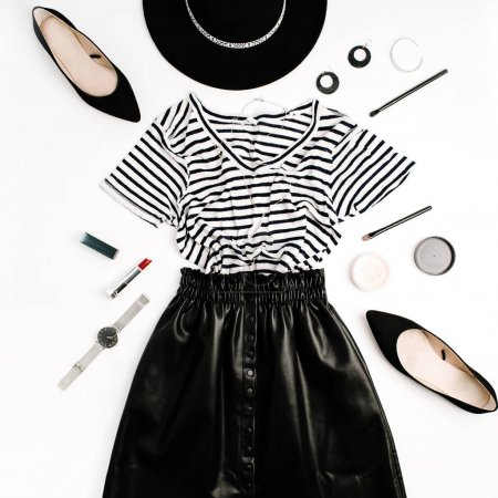 Woman fashion flatlay. Black modern clothes and accessories. Skirt, t-shirt, hat, shoes, lipstick, watches, powder on white background. Flat lay, top view.
