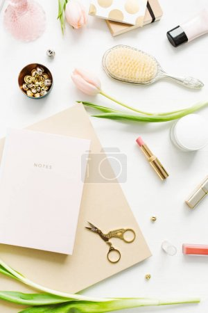 Women home office desk with pink tulip flowers, notebook, accessories and cosmetics on white background. Flatlay, top view fashion blog composition.