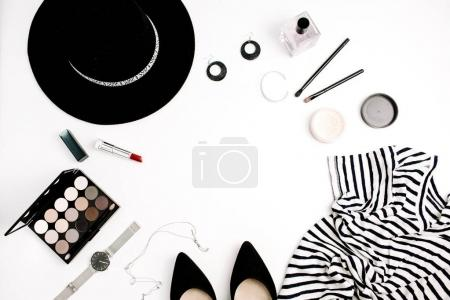 Woman fashion flatlay. Frame of modern clothes, accessories and cosmetics. T-shirt, hat, shoes, palette, lipstick, watches, powder on white background. Flat lay, top view.
