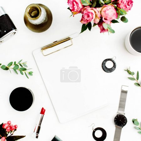 Female home office workspace with clipboard, laptop, rose flowers, eucalyptus branches, fashion accessories and cosmetics. Flat lay, top view fashion mockup this space for text.