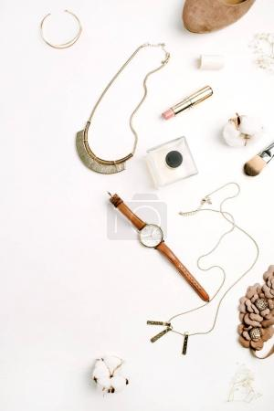 Flat lay fashion composition. Female accessories: shoes, watches, perfume, lipstick, bracelet, necklace on white background. Top view.