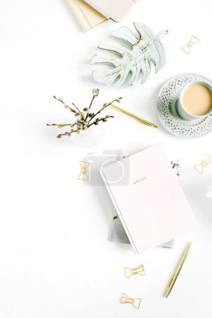 Home office desk table. Flatlay of workspace with pale pastel pink notebook and decorations on white background. Flat lay, top view.