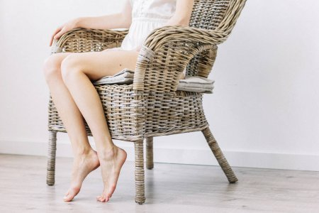 Beautiful young woman in straw chair.