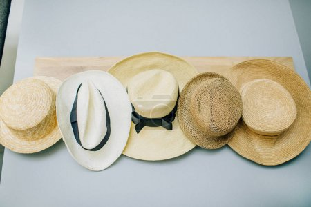 Straw hats collection on pastel blue background.