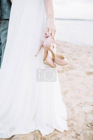 High heel shoes in young woman hands on beach.