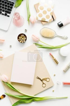Female home office desk workspace with laptop, pink tulip flowers, notebook, accessories and cosmetics on white background. Flat lay, top view fashion blog composition.