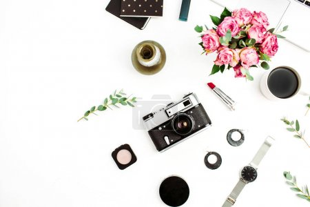 Feminine stylish home desktop with photo camera, accessories, rose flowers, eucalyptus and cosmetics. Flatlay, top view fashion blog background.