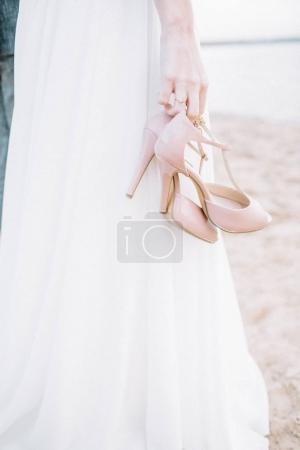 Young woman on beach holding high heel shoes.