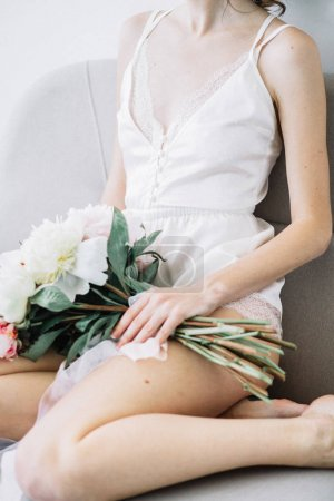 Young beautiful woman with peony flowers bouquet on white sofa.