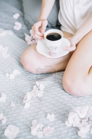 Photo for Young woman in underwear holding cup of coffee and cookie. - Royalty Free Image