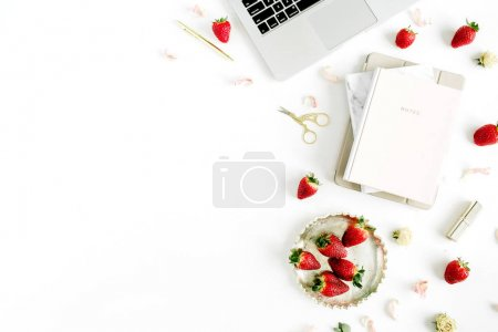 Women's workspace with with laptop, notebook, lipstick, fresh strawberry on white background. Flat lay, top view.