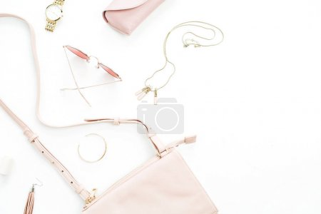 Woman fashion trendy accessories set: purse, sunglasses, watch, bracelet, necklace, lipstick, earrings on white background. Flat lay, top view stylish pastel pink concept.