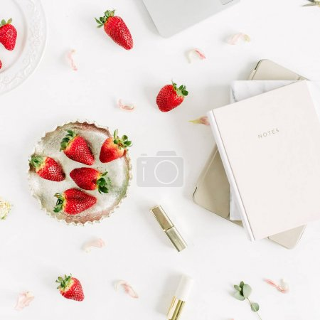 Women's modern home office desk workspace with laptop, notebook, lipstick, fresh raw strawberries and rose flower buds on white background. Flat lay, top view.