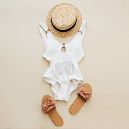 Flat lay summer fashion composition. Women's swimsuit, straw and slippers on pastel beige background. Flat lay, top view minimal beach concept.