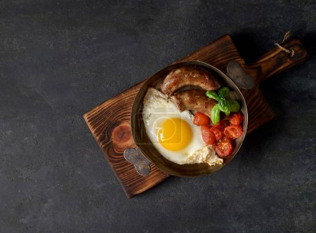 Photo for Breakfast in a frying pan, fried eggs, sausages and tomatoes on a dark background - Royalty Free Image