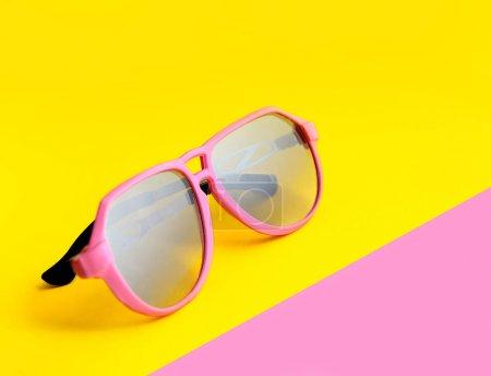 Pink sunglasses on yellow
