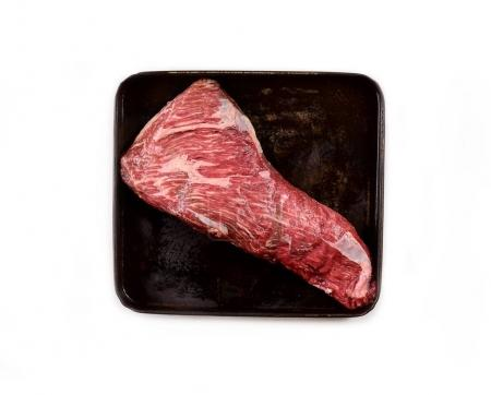 raw meat on a baking sheet on black background