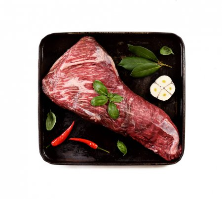 raw meat on a baking sheet on black pan isolated on white
