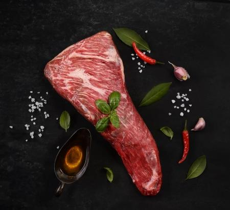 raw meat on wooden cutting board with vegetables