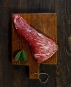 raw meat on wooden cutting board with basil leaves
