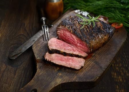 sliced grilled steak with rosemary on cutting board on black background, close up