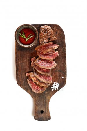 grilled steak with spices on wooden cutting board isolated on white background