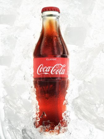POLTAVA, UKRAINE - MARCH 22, 2018: Classic Coca-Cola bottle with ice. Coca Cola drinks are produced and manufactured by The Coca-Cola Company, an American multinational beverage corporation