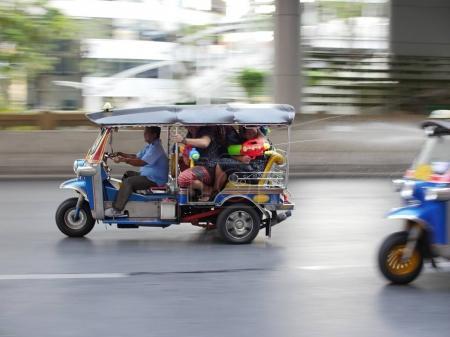 Menschen greifen andere Tuktuk mit Wasserpistolen während Songkran an Narathiwas Straße in Bangkok an