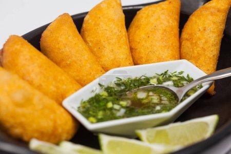 Photo pour Empanadas colombiens typiques servis avec une sauce épicée sur un plat traditionnel en céramique noire - image libre de droit
