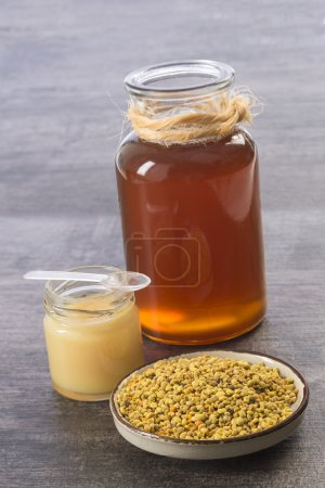 Golden bee pollen iin a cup with royal jelly and honey in jar glass