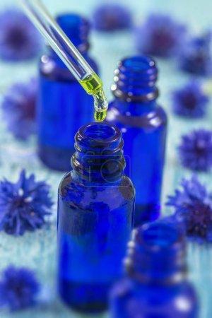 Photo pour Bouteilles en verre bleu avec gouttes liquide essentiel dans compte-gouttes. Concentration sélective. Focus sur compte-gouttes . - image libre de droit