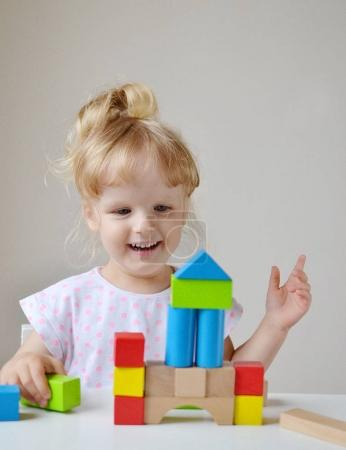 Caucasian Girl Playing with Wooden Colorful Cubes at Home