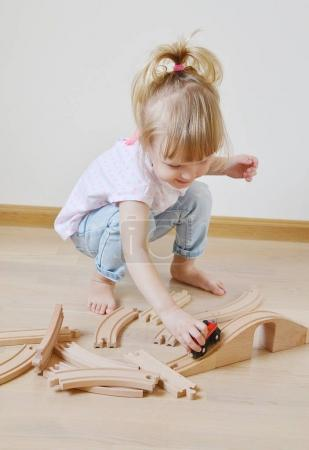 Caucasian Girl Playing with Wooden Railway at Home