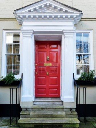 Photo pour Belle maison avec fenêtres et porte d'entrée rouge - image libre de droit