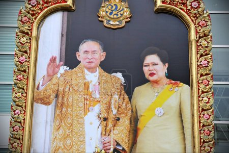Bangkok, Thailand - December 2, 2012: large portrait of Thai King and Queen adorns shop front in city center