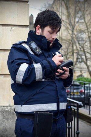 London, UK - December 30, 2017: Highways Agency Traffic Officer writes ticket for motoring violation on city street