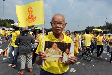 BANGKOK - December, 5: royalist holds portrait of Thai King Bhumibol Adulyadej while attending celebrations of King's 85th birthday