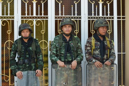 three soldiers standing near metal fence